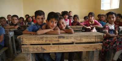 "Muhannad (L), Ahmad (C), And Ali (R), All 8 Years Old, Sit In A Classroom In Teabat Al Reah School In The Zumar Sub-district Of Ninewa Governorate. They Have Returned To Zumar Earlier This Year After Being Displaced Due To Conflict In The Area Last Year.  ""I Didn't Know That I Would Meet My Friends Again,"" Said Muhannad. ""I Don't Want To Go Back Those Days [of Being Displaced]. I Hope Everybody Can Return To Their Homes.""  UNICEF Implementing Partner People In Need (PIN) Is Facilitating The Reopening Of 10 Schools And The Enrollment Of Returnee Students In The Zumar Sub-district Of Ninewa Governorate After Armed Groups Were Forced To Retreat From The Area Earlier This Year And Displaced Families Were Able To Return Home.  Most Schools In Zumar Are Now Open And Children Have Returned To Class, But The Buildings Are In Dire Need Of Reconstruction - Some Lack Proper Water And Sanitation, Gender Separate Bathrooms, Or Their Equipment Was Looted During The Conflict. Some Parents Are Still Afraid To Send Their Children To School, Especially If The School Is Far Away. There Are Very Few Women Teachers, Which Makes It More Difficult For Female Students To Attend.   Most Students Who Are Now Returning To Class Have Missed Months Of Education While They Were Displaced From The Area Due To Conflict. After The Turmoil Of Displacement, Restoring Access To Education Is Essential.  With Generous Contributions From The Governments Of Canada, Japan, Ireland And Germany, In The Last Year As Part Of The Overall Response To The Crisis In Iraq, UNICEF And Parters Provided Access To Education To Nearly Half A Million Children Through Building New Schools, Installing Prefabricated Classrooms, Establishing Temporary Learning Spaces, And Distributing Learning Materials.  However, The Impact Of Conflict, Violence And Displacement Has Devastated Iraq's Education System. Nearly 2 Million Children Are Currently Out Of School, With An Additional 1.2 Million At Risk Of Dropping Out. Almost 1 In"
