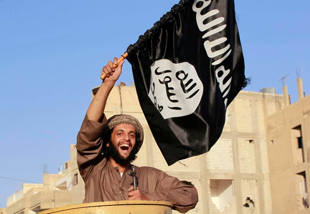 "A militant Islamist fighter waving a flag, cheers as he takes part in a military parade along the streets of Syria's northern Raqqa province June 30, 2014. The fighters held the parade to celebrate their declaration of an Islamic ""caliphate"" after the group captured territory in neighbouring Iraq, a monitoring service said. The Islamic State, an al Qaeda offshoot previously known as Islamic State in Iraq and the Levant (ISIL), posted pictures online on Sunday of people waving black flags from cars and holding guns in the air, the SITE monitoring service said. Picture taken June 30, 2014. REUTERS/Stringer (SYRIA - Tags: POLITICS CIVIL UNREST CONFLICT) - RTR3WKMT"